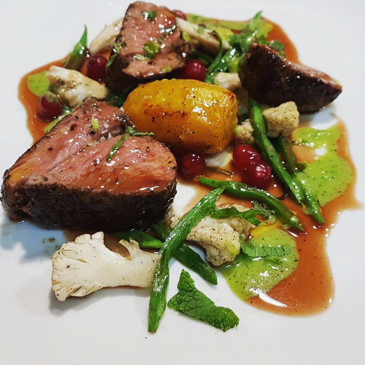 Rump of Irish lamb, pea puree, roasted cauliflower, mint leaves & red current juices